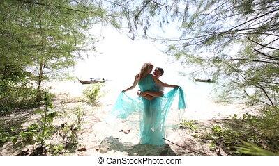 guy embraces blonde girl at back