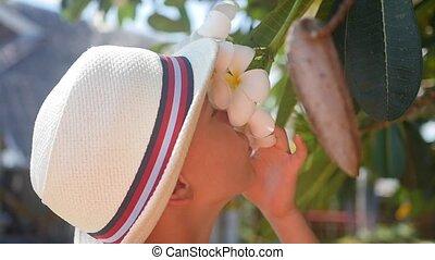 guy enjoying the scent of flowering tropical trees.Plumeria...