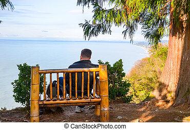 Guy enjoys views of the Black Sea on the bench botanical garden. Georgia, Batumi.