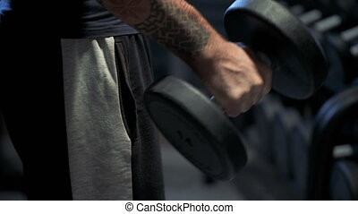 Guy flexing arms with dumbbells in his hands, gym workout,...