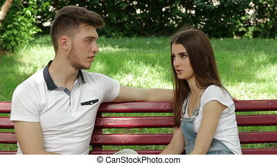 guy flirts and amuses the girl in the Park on a bench