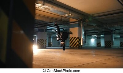 Guy freerunner doing a series of jumps, somersaults and...