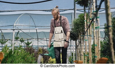 Guy gardener going to the greenhouse, watering plants from a green funnel. The garden center is green plants and bright flowers.