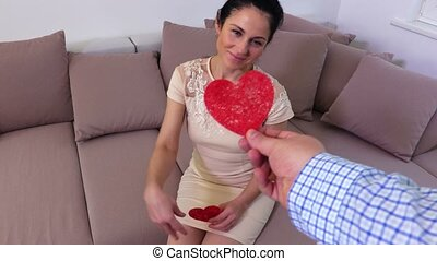 Guy gives the woman a red paper heart