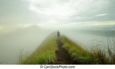 A guy walks along the road and disappears in the fog.