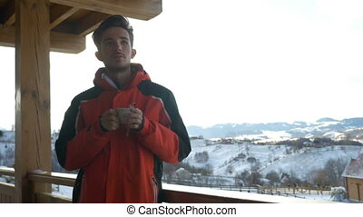 Guy grabbing a cup of hot beverage from a wooden railing on...