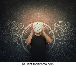 Guy hiding face holding a clock instead of head stands over dark blackboard with drawn gears and cogwheels