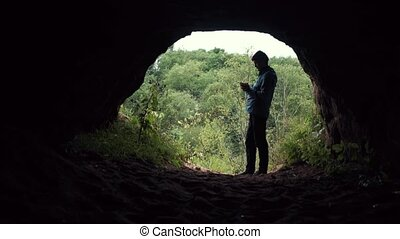Guy hiker smartphone standing near exit from cave. Deep...