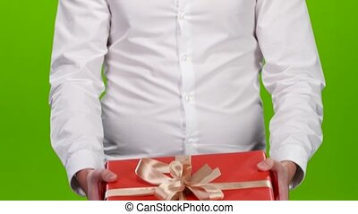 Guy holding out a box with a gift. Close up