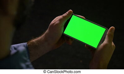 Guy holding showing and pointing at smart phone with green screen in hands