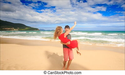 Guy Holds in Arms Circles Blond Girl Makes Selfie on Beach