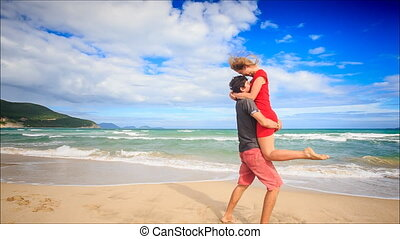 Guy Holds in Arms Circles Kiss Blond Girl on Beach Wave Surf