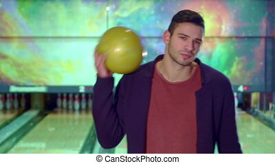 Guy holds the bowling ball on his shoulder