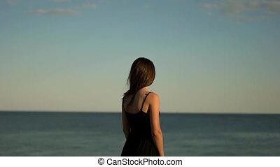 Guy hugs a girl in black by the sea