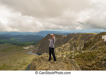 Guy in a gray sweatshirt with a cap is standing with his hands apart on the edge of the cliff in front of him is a colorful view of mountains lakes with glaciers. Traveler complete the route
