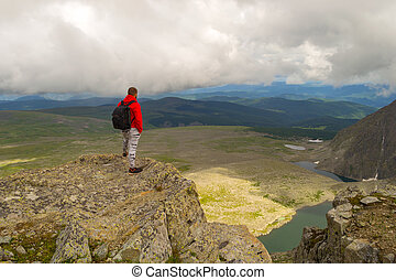 Guy in a red sweatshirt with a backpack is standing with his hands in pockets on the edge of the cliff in front of him is a colorful view of mountains lakes with glaciers. Traveler complete the route