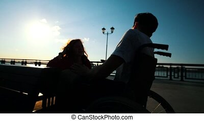 Guy In A Wheelchair Talking To A Girl In Evening At Sunset,...