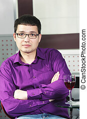 Guy in cafe with glass of wine arms folded