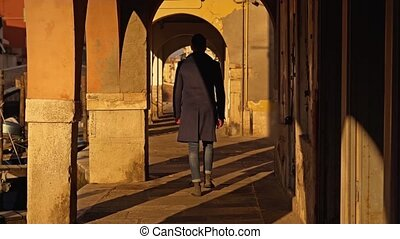 Guy in stylish long dark coat walks along arch passage on city embankment past old channel at sunset in Chioggia backside view