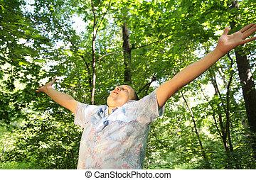 Guy in dark woods with raised hands