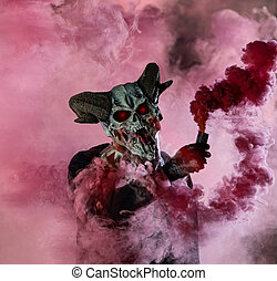 guy in devil mask standing with smoke bombs