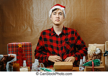 Guy in plaid shirt and Santa hat in Christmas decorations.