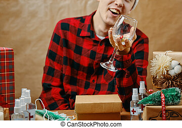 Guy in plaid shirt holds a glass with drugs and pills.