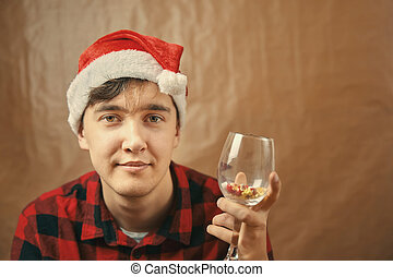 Guy in Santa Claus hat holds a glass with various pills.