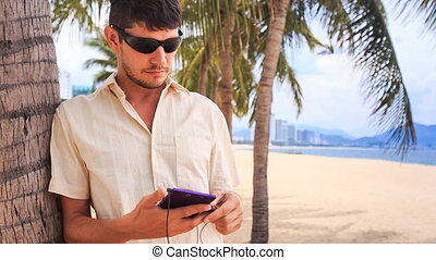 guy in sunglasses operates iphone under palm tree on sand beach