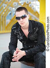 guy in sunglasses sits on yellow footbridge