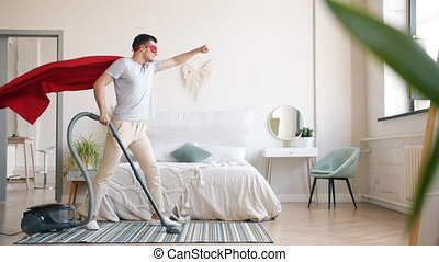 Guy in superman costume cleaning carpet with vacuum cleaner in bedroom at home