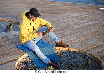 Guy in the yellow jacket and black cap sitting on the pier with a tablet