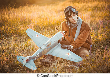 Guy in vintage clothes pilot with an airplane model outdoors...