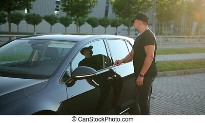 Guy inspects car from outside before the purchase it in car dealership. Medium shot of man inspecting vehicle. Young attractive human