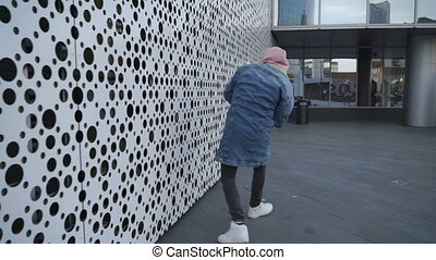 Guy is dancing next to perforated wall