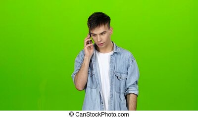 Guy is flirting with his girlfriend on the phone. Green screen