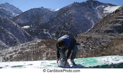 Guy is having fun with the spring snow posing camera in winter beautifull mountains landscape in Almaty