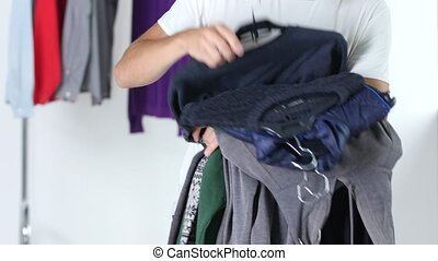 Guy is holding the clothes - Guy holding clothes in his...