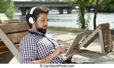 Guy is lying on bench and listening to music through headphones. Also he is holding tablet and typing on screen. Man is looking at screen and moving his fungers. He slides down and up. Guy is smiling.