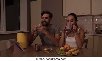 Guy is sitting down in chair and looking at girl. She looks at him too and drinks from cup. They are smiling to each other. There are bowl with fruit and tablet on the table.
