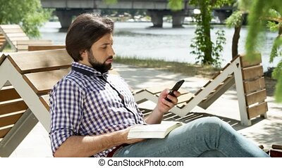 Guy is sitting on bench and reading a book. Then he got...