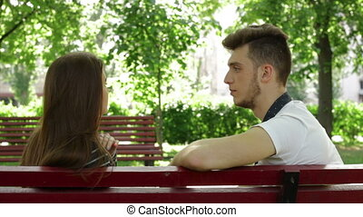 guy is talking to a beautiful young girl on a bench in the Park