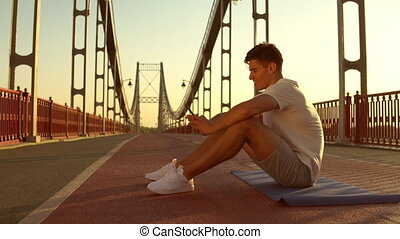 guy is texting after intensive workout - man using his...