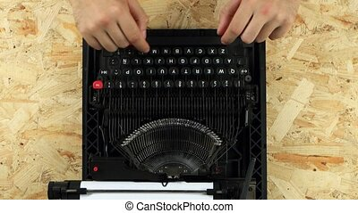 Guy is typing on a printed retro typewriter. View from above