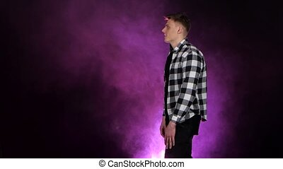 Guy is waiting for his girlfriend, she comes, he turns her around. Multi colored smoke background