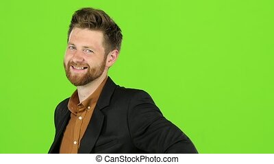 Guy jokes, he is not bored, he is happy and positive. Green screen. Slow motion