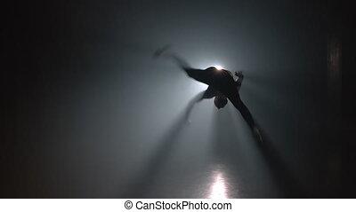 Guy jumping double sideflip on floodlight background in slow motion. Night tricking, making kick. Man demonstrates extreme tricks in smoke dark studio.
