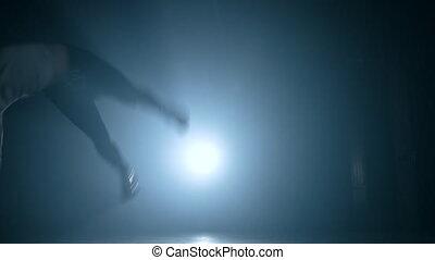 Guy jumping double sideflip on floodlight background in slow motion. Night tricking, making kick. Man demonstrates extreme tricks in smoke dark studio .