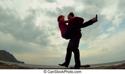 Guy keeps the girl in his arms - Young couple on the beach....