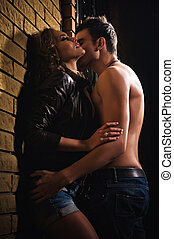 Sexy couple kissing against a wall